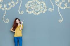 Progettista sorridente che indica la parete mentre mostrando un ornamento del fiore Immagini Stock