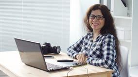 Progettista sorridente della donna che lavora al computer in ufficio video d archivio