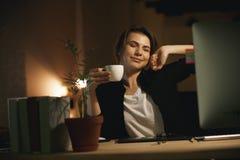 Progettista sorridente della giovane donna che allunga all'interno alla notte Immagine Stock Libera da Diritti