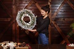 Progettista sorridente sveglio che mostra a Natale la corona sempreverde dell'albero Giovane donna che tiene la corona di natale  immagini stock