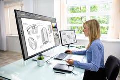 Progettista Using Graphic Tablet mentre lavorando al computer fotografia stock libera da diritti