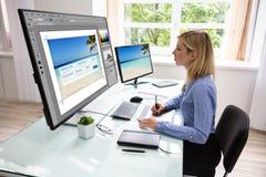 Progettista Using Graphic Tablet mentre lavorando al computer fotografia stock
