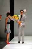 Progettista Zac Posen che riceve mazzo dei fiori dopo il suo manifestazione ad Audi Fashion Festival 2012 Immagine Stock