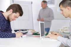 Progettisti maschii che lavorano al computer portatile alla classe Immagine Stock Libera da Diritti