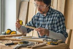 Progetto di pianificazione DIY del carpentiere nell'officina della lavorazione del legno immagini stock