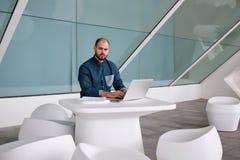 progetto di sviluppo dell'architetto maschio di costruzione tramite computer portatile mentre sedendosi nell'interno moderno dell Fotografia Stock Libera da Diritti