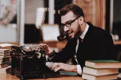 progetto Uomo d'affari vestito siedasi Vecchia macchina da scrivere fotografie stock