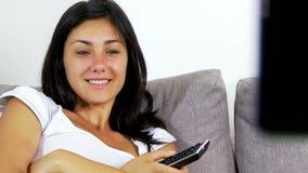Program för tv för lycklig flicka hållande ögonen på roligt hemma arkivfilmer