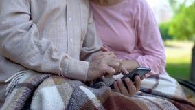 Programa aposentado do smartphone da consultação dos pares, sentando-se no parque, candidatura online imagem de stock royalty free