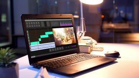 Programa de editor de v?deo sobre el ordenador port?til en la oficina de la noche almacen de video