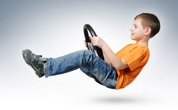 Programa piloto de coche divertido del muchacho con el volante Imagen de archivo libre de regalías