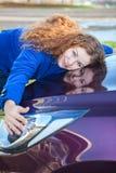 Programa piloto femenino joven que abraza el capo motor del vehículo Fotografía de archivo libre de regalías
