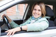 Programa piloto femenino que se sienta en coche y que sostiene la rueda Foto de archivo libre de regalías