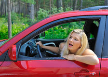 Programa piloto hermoso de la mujer en coche brillante rojo al aire libre Imagen de archivo