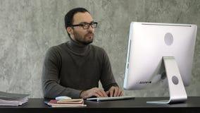 programación Hombre que trabaja en el ordenador en él la oficina, sentándose en los códigos de la escritura del escritorio Código foto de archivo
