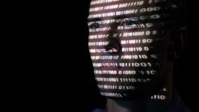 Programador adulto del hombre con la barba que mira una pantalla de monitor mientras que los caracteres de código binario se proy metrajes