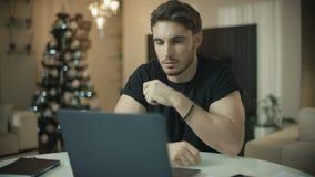 Programador del hombre que trabaja en el ordenador portátil en el hogar del Año Nuevo Trabajador independiente de sexo masculino almacen de metraje de vídeo