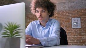 Programador divertido del empollón con la codificación del pelo rizado en el ordenador portátil y sentada en la tabla en oficina  almacen de metraje de vídeo