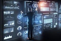 Programador elegante que está na frente de um dispositivo e de um trabalho transparentes gigantes Imagens de Stock