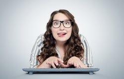 Programador engraçado feliz da moça nos vidros com o teclado na frente do computador foto de stock