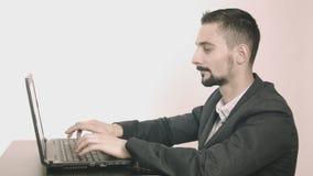 Programador hombre-ordenador del negocio que mecanografía en su escritorio y que mira la cámara almacen de metraje de vídeo