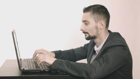 Programador hombre-ordenador del negocio que mecanografía en su escritorio y que mira la cámara almacen de video