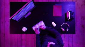 Programador o pirata informático del hombre joven que trabaja en el ordenador en la noche almacen de metraje de vídeo