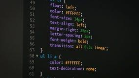 Programador que enrolla hacia arriba y hacia abajo para corregir la página del editor de código del sitio web del HTML css metrajes