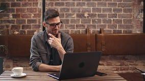 Programador Typing en el ordenador portátil en café metrajes