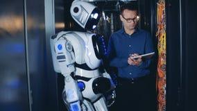 Programador y robot, trabajo del varón las TIC del droid en un centro de datos