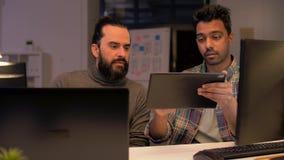 Programadores com o PC da tabuleta que trabalha no escritório da noite video estoque