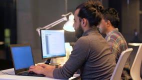 Programadores com os computadores que trabalham tarde no escritório vídeos de arquivo