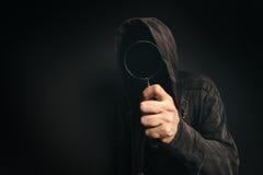 Programas informáticos del Spyware, persona fantasmagórica encapuchada con magnificar Fotografía de archivo