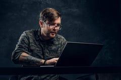 Programista jest ubranym modnego militarnego koszulowego działanie na laptopu obsiadaniu przy stołem w biurze zdjęcia stock