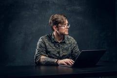 Programista jest ubranym modnego militarnego koszulowego obsiadanie przy stołem z laptopem w biurze przeciw ciemnej ścianie zdjęcia stock