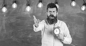 Programma en regimeconcept Gebaarde hipster houdt klok, bord op achtergrond, exemplaarruimte Mens met baard  royalty-vrije stock afbeeldingen