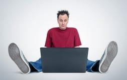 Programmatore che si siede sul pavimento davanti ad un computer portatile immagini stock libere da diritti