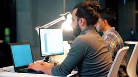 Programmatore con i computer che funzionano all'ufficio di notte stock footage