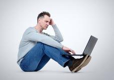 Programmatore con il computer portatile che si siede sul pavimento Fotografie Stock Libere da Diritti