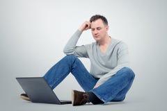 Programmatore con il computer portatile che si siede sul pavimento Fotografia Stock