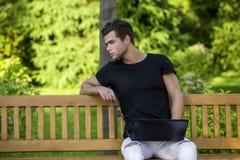 Programmatore con il taccuino che si siede nel parco di autunno Fotografia Stock Libera da Diritti