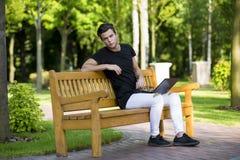 Programmatore con il taccuino che si siede nel parco di autunno Fotografie Stock