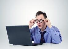 Programmatore in vetri con il computer portatile immagine stock