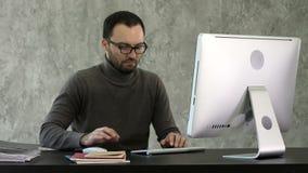programmazione Uomo che lavora al computer in ufficio, sedentesi ai codici di scrittura dello scrittorio Codice di dati di battit stock footage