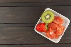 Programme de régime, nourriture crue Kiwi, fraise et pamplemousse rouge dans un plat de porcelaine Images libres de droits