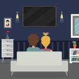 Programme télévisé de observation de femme et d'homme à la maison Image libre de droits