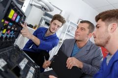 Programmer apprentices fixing continuous ink supply system. Printer royalty free stock photo