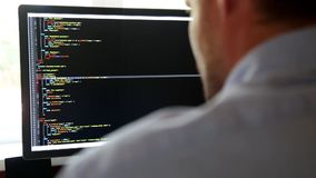 Programmer from behind and programming code on computer monitor stock footage