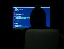 Programmer in dark room. Programmer in hoodie typing code in dark room Stock Image
