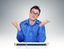Programmer with glasses behind the keyboard. Royalty Free Stock Images